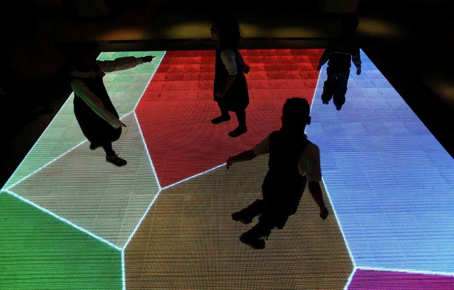 "Children run across an interactive exhibit at the new National Museum of Mathematics in New York, Monday, Dec. 17, 2012. The museum is aimed at kids aged 8 to 13, and curators have given the place a playground feel. The 40 exhibits include a ""wall of fire"" made up of laser lights that teaches kids about geometry and a square-wheeled tricycle that still manages to produce a smooth ride thanks to a wavy track. Photo: Seth Wenig, AP / AP"
