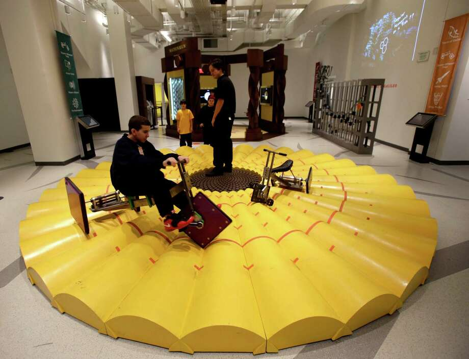 "A visitor to the new National Museum of Mathematics rides a tricycle with square wheels in New York, Monday, Dec. 17, 2012. The museum is aimed at kids aged 8 to 13, and curators have given the place a playground feel. The 40 exhibits include a ""wall of fire"" made up of laser lights that teaches kids about geometry and a square-wheeled tricycle that still manages to produce a smooth ride thanks to a wavy track. Photo: Seth Wenig, AP / AP"