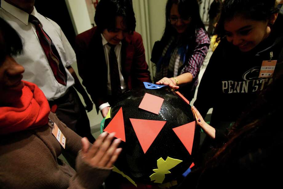 "Students visiting the new National Museum of Mathematics put shapes on a three-dimensional surface in New York, Monday, Dec. 17, 2012. The museum is aimed at kids aged 8 to 13, and curators have given the place a playground feel. The 40 exhibits include a ""wall of fire"" made up of laser lights that teaches kids about geometry and a square-wheeled tricycle that still manages to produce a smooth ride thanks to a wavy track. Photo: Seth Wenig, AP / AP"