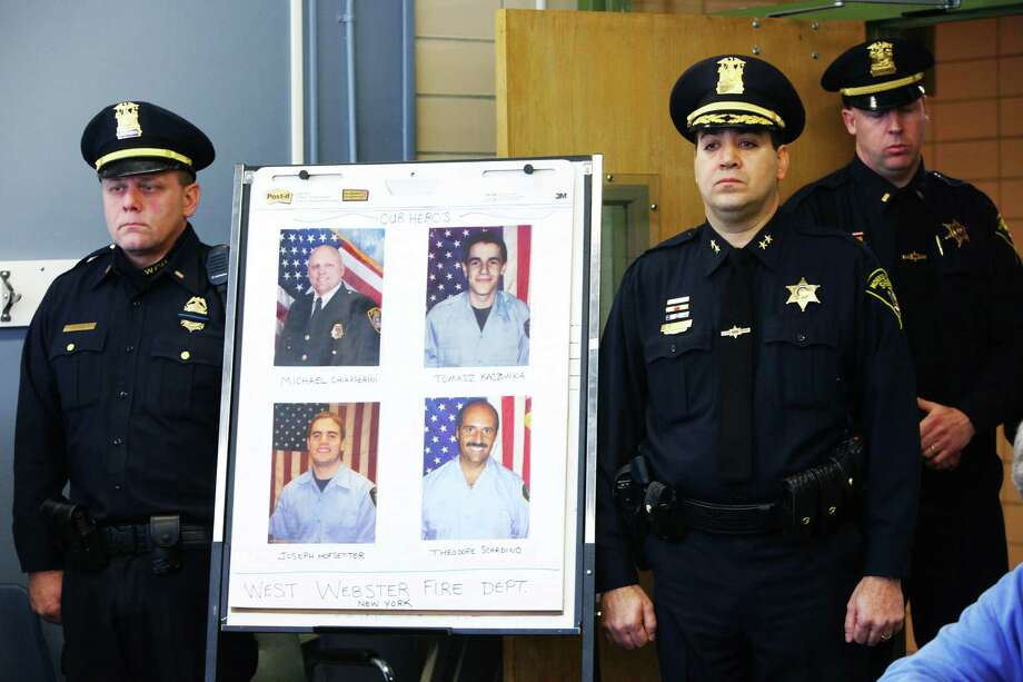 Monroe County Sheriff Deputy Chief Steve Scott, second from right, and Webster Police Lt. Joseph Rieger stand by the photo of the dead and injured firefighters during a news conference in Webster, N.Y., Tuesday, Dec. 25, 2012. Authorities say William Spengler, 62, who served 17 years in prison for manslaughter in the 1980 hammer slaying of his grandmother, set his house afire then sprayed bullets at first responders, killing two firefighters and injuring two others. He then killed himself as seven houses burned on a sliver of land along Lake Ontario. Photo: Marie De Jesus, AP / Democrat & Chronicle