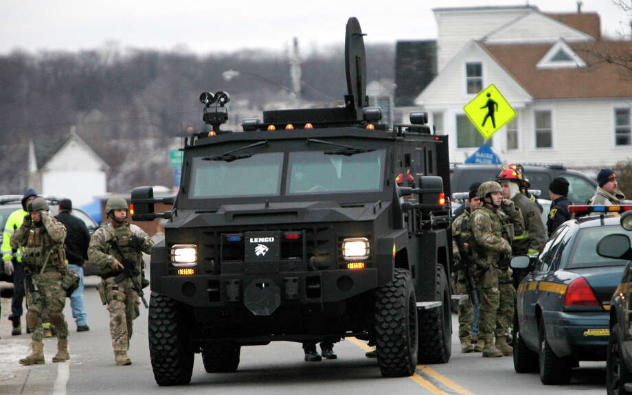 A Monroe County Sheriff's Department armored truck drops off residents who were evacuated from the neighborhood, Monday, Dec. 24, 2012 in Webster, New York. A former convict set a house and car ablaze in his lakeside New York state neighborhood to lure firefighters then opened fire on them, killing two and engaging police in a shootout before killing himself while several homes burned. Authorities used an armored vehicle to evacuate the area. Photo: Max Schulte, AP / Democrat & Chronicle