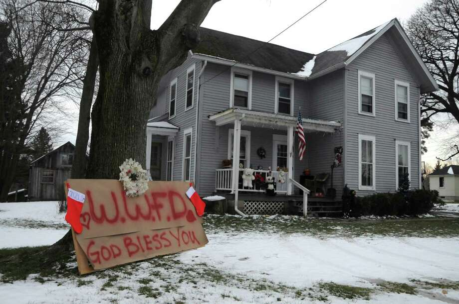 "A makeshift memorial that says ""W.W.F.D. God Bless You"" sits in front of a home in  Webster, N.Y., Monday, Dec. 24, 2012. An ex-con set a car and a house ablaze in his lakeside neighborhood to lure firefighters, then opened fire on them, killing two, engaging in a shootout with police and committing suicide while several homes burned. Authorities used an armored vehicle to evacuate the area. Photo: Jack Haley, AP / Messenger Post Media"