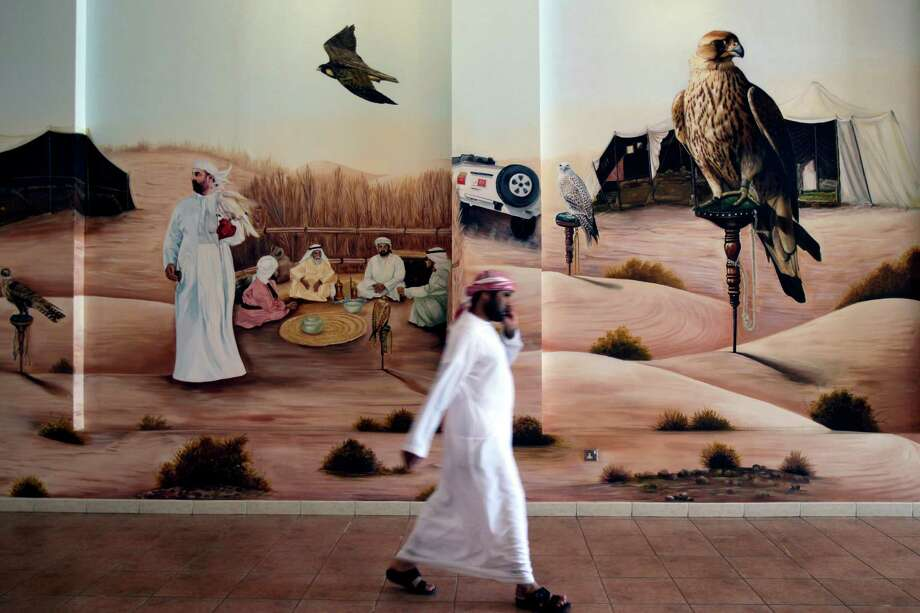 In this Wednesday, Nov. 14, 2012 photo, an Emirati man passes in front of a wall painting showing the traditional falcon hunting images at the Falcon Center in Dubai, United Arab Emirates. Visitors and tourists to Dubai have shown great enthusiasm to the National Falcon Centre at Nad Al Sheba, which offers sale of falcons and all accessories related to falconry. While the methods to develop top-quality hunting falcons date back to antiquity, its transition into a modern Middle Eastern passion has brought in microchip tagging and price tags that can run well over $10,000 for a prime bird. Photo: Kamran Jebreili, AP / AP