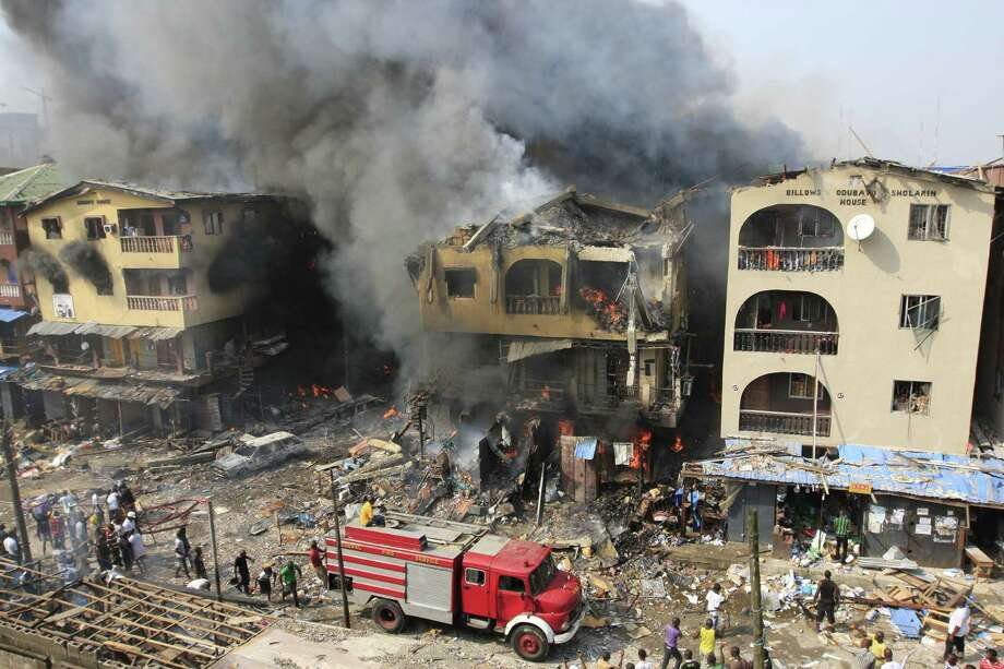 A fire truck passes a warehouse on fire on Lagos Island in Lagos, Nigeria, on Wednesday, Dec. 26, 2012. An explosion ripped through a warehouse Wednesday where witnesses say fireworks were  stored in Nigeria's largest city, sparking a fire. It wasn't immediately clear if anyone was injured in the blast that firefighters and locals struggled to contain. Photo: Jon Gambrell, AP / AP