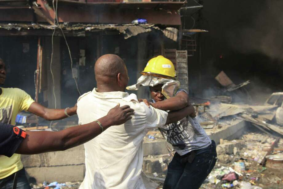 Men fight over a fire helmet as a fire burns on Lagos Island in Lagos, Nigeria, on Wednesday, Dec. 26, 2012. An explosion ripped through a warehouse Wednesday where witnesses say fireworks were  stored in Nigeria's largest city, sparking a fire. It wasn't immediately clear if anyone was injured in the blast that firefighters and locals struggled to contain. Photo: Jon Gambrell, AP / AP