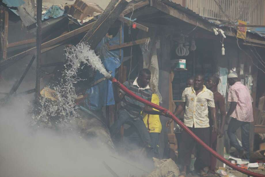 Local men try to fight a fire on Lagos Island in Lagos, Nigeria, on Wednesday, Dec. 26, 2012. An explosion ripped through a warehouse Wednesday where witnesses say fireworks were  stored in Nigeria's largest city, sparking a fire. It wasn't immediately clear if anyone was injured in the blast that firefighters and locals struggled to contain. Photo: Jon Gambrell, AP / AP
