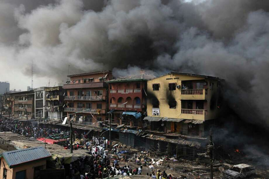 Residents look  as a fire burns out a residential homes and a warehouse on Lagos Island in Lagos, Nigeria, Wednesday, Dec. 26, 2012. An explosion ripped through a warehouse Wednesday where witnesses say fireworks were stored in Nigeria's largest city, sparking a fire. It wasn't immediately clear if anyone was injured in the blast that firefighters and locals struggled to contain. Photo: Sunday Alamba, AP / AP