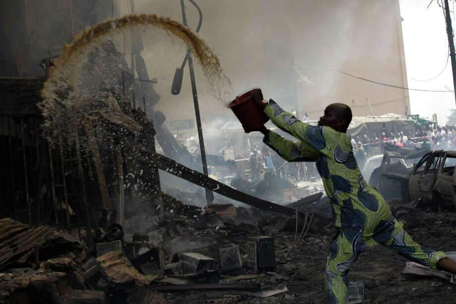 A man tries to contain fire at a burnt out warehouse on Lagos Island in Lagos, Nigeria, Wednesday, Dec. 26, 2012. An explosion ripped through a warehouse Wednesday where witnesses say fireworks were stored in Nigeria's largest city, sparking a fire. It wasn't immediately clear if anyone was injured in the blast that firefighters and locals struggled to contain. Photo: Sunday Alamba, AP / AP