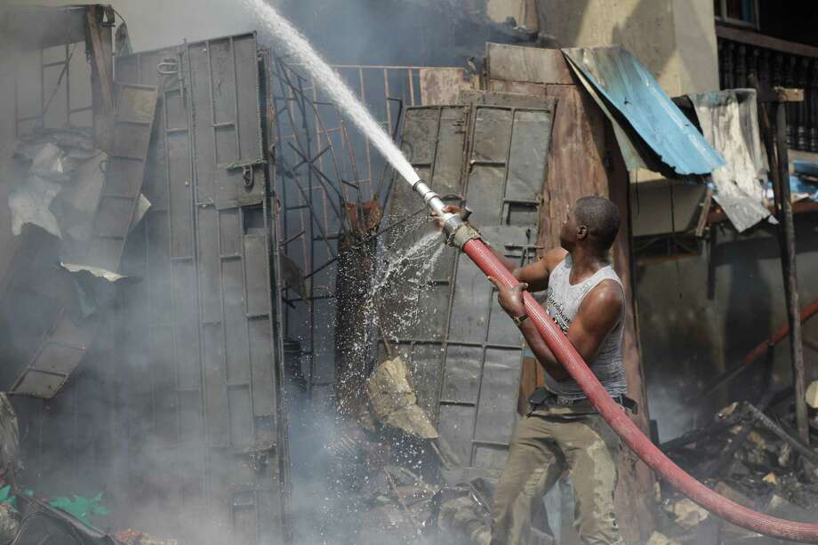 A firefighter  tries to contain fire at a burnt out warehouse on Lagos Island in Lagos, Nigeria, Wednesday, Dec. 26, 2012. An explosion ripped through a warehouse Wednesday where witnesses say fireworks were stored in Nigeria's largest city, sparking a fire. It wasn't immediately clear if anyone was injured in the blast that firefighters and locals struggled to contain. Photo: Sunday Alamba, AP / AP