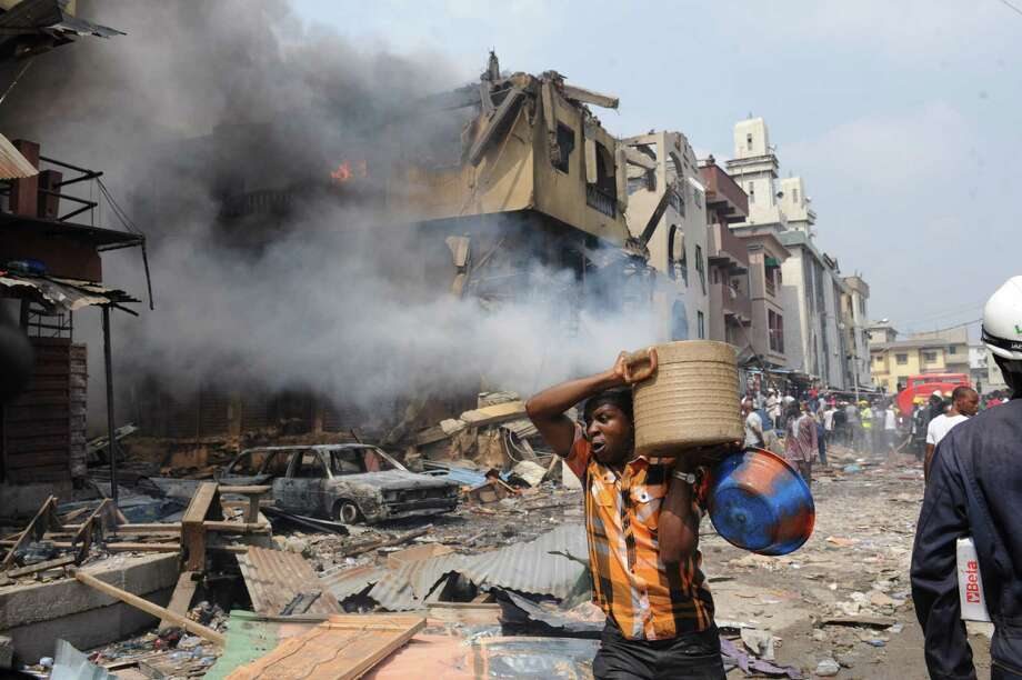 A man carries good salvaged from building stocked with fireworks on fire in Lagos on December 26, 2012. Fire ripped through a crowded neighbourhood in Nigeria's largest city and wounded at least 30 people after a huge explosion rocked a building believed to be storing fireworks, officials said.   AFP PHOTO/PIUS UTOMI EKPEIPIUS UTOMI EKPEI/AFP/Getty Images Photo: PIUS UTOMI EKPEI, AFP/Getty Images / AFP