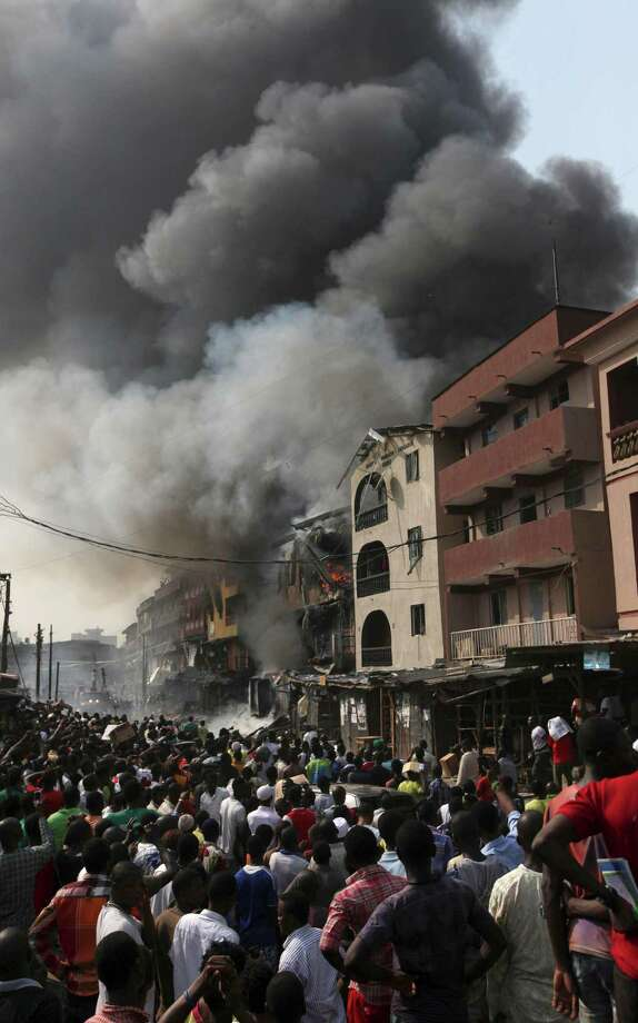 People gather at the site of a  a fire at a warehouse on Lagos Island in Lagos, Nigeria, Wednesday, Dec. 26, 2012. An explosion ripped through a warehouse Wednesday where witnesses say fireworks were stored in Nigeria's largest city, sparking a fire. It wasn't immediately clear if anyone was injured in the blast that firefighters and locals struggled to contain. Photo: Sunday Alamba, AP / AP