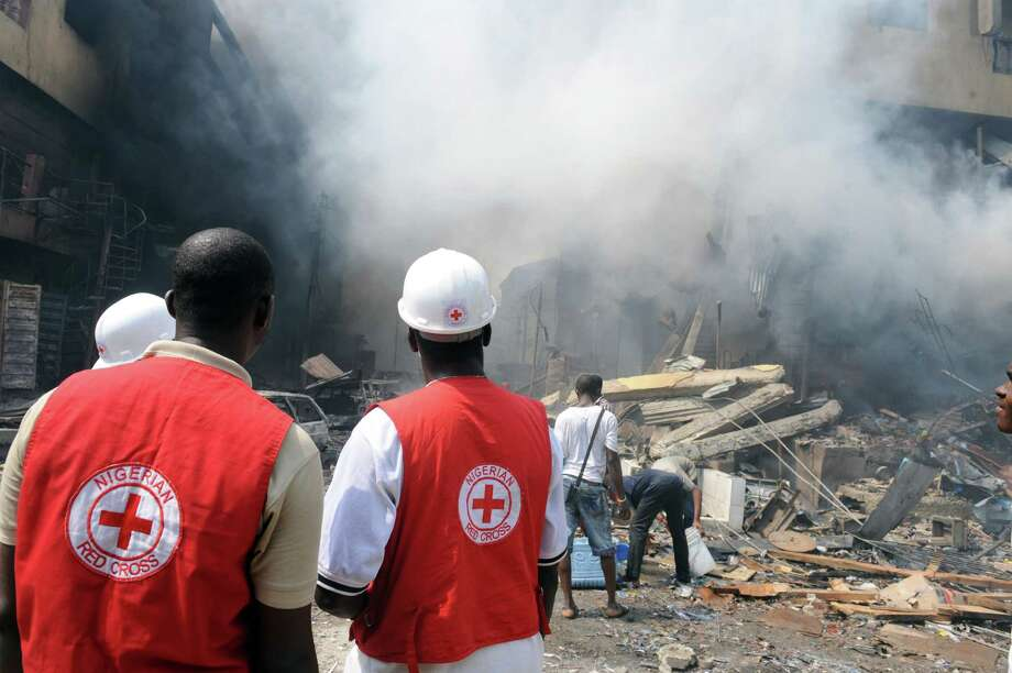 Red Cross officials walk look at a building on fire after a heavy explosion on December 26, 2012 in Lagos. Fire ripped through a crowded neighbourhood in Nigeria's largest city and wounded at least 30 people after a huge explosion rocked a building believed to be storing fireworks, officials said.  Fireworks continued to explode well after the fire began while smoke was heavy and the blaze intense, making it difficult for rescue workers and firefighters to approach the scene. AFP PHOTO/PIUS UTOMI EKPEIPIUS UTOMI EKPEI/AFP/Getty Images Photo: PIUS UTOMI EKPEI, AFP/Getty Images / AFP
