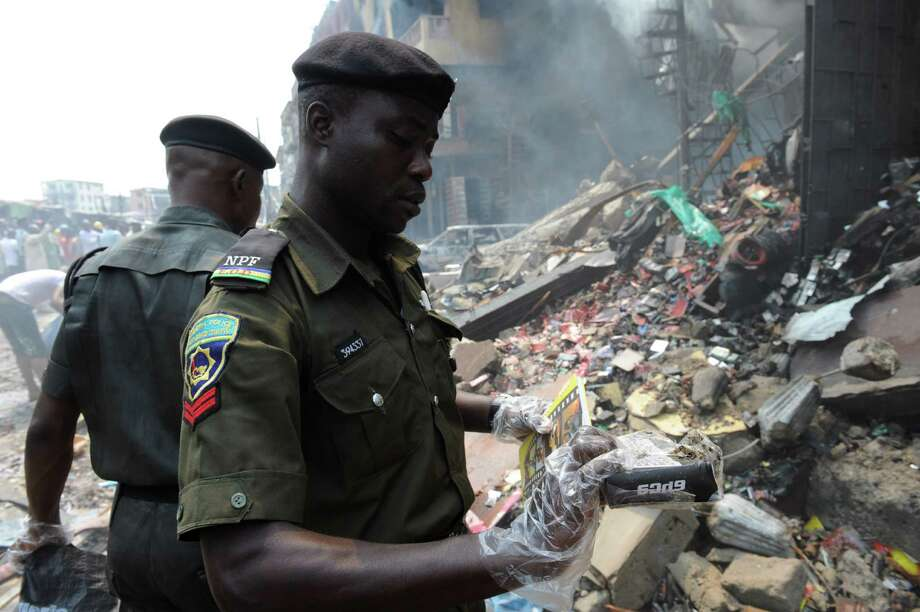 Anti-bomb policemen collect debris for examination at the scene of an explosion in a building in Lagos on December 26, 2012. Fire ripped through a crowded neighbourhood in Nigeria's largest city and wounded at least 30 people after a huge explosion rocked a building believed to be storing fireworks, officials said.  AFP PHOTO/PIUS UTOMI EKPEIPIUS UTOMI EKPEI/AFP/Getty Images Photo: PIUS UTOMI EKPEI, AFP/Getty Images / AFP