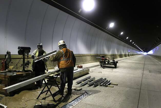 Lawrence Sumerlin (left) and Ron McKibben work in one of the 4,200-foot tunnels, which will each hold a single lane of traffic. Photo: Paul Chinn, The Chronicle