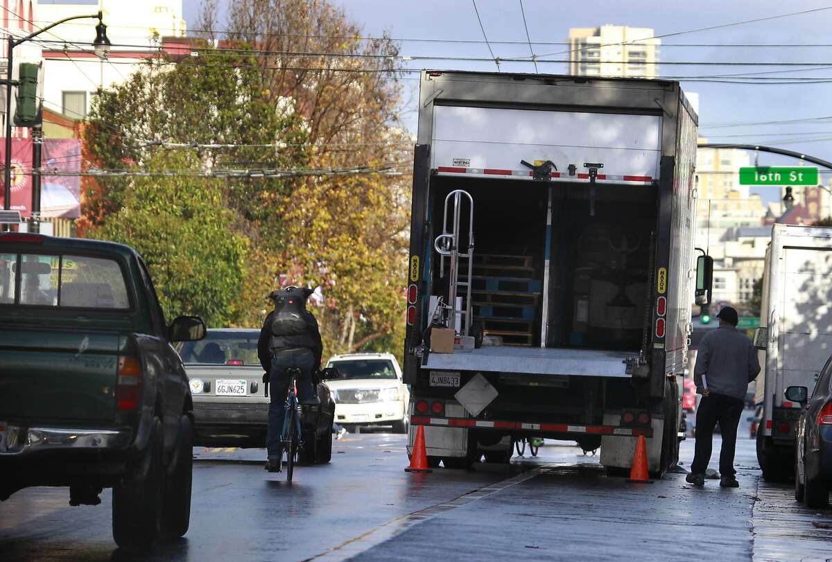 A bicyclist is forced to swerve into a traffic lane by a truck that double parked in the bike lane while making a delivery on Valencia Street near 16th Street in San Francisco, Calif. on Wednesday, Dec. 26 2012.