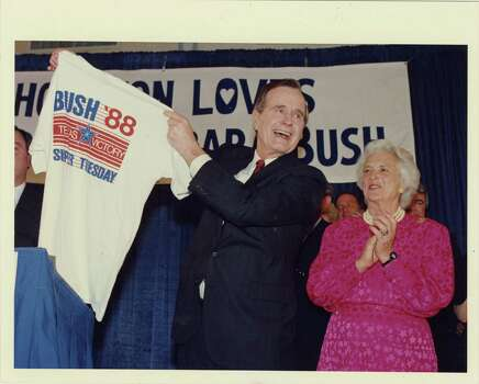 "03/08/1988 - Celebrating his Super Tuesday election night victory, Vice President George Bush holds up a ""Bush '88, Texas Victory"" t-shirt at the Westin Oaks Hotel ballroom in Houston. The shirt was presented to him by GOP state co-chair, Tom Loeffler. His wife, Barbara, stands beside him. Bruce Bennett / Houston Post Photo: Bruce Bennett, Houston Chronicle / Houston Post files"