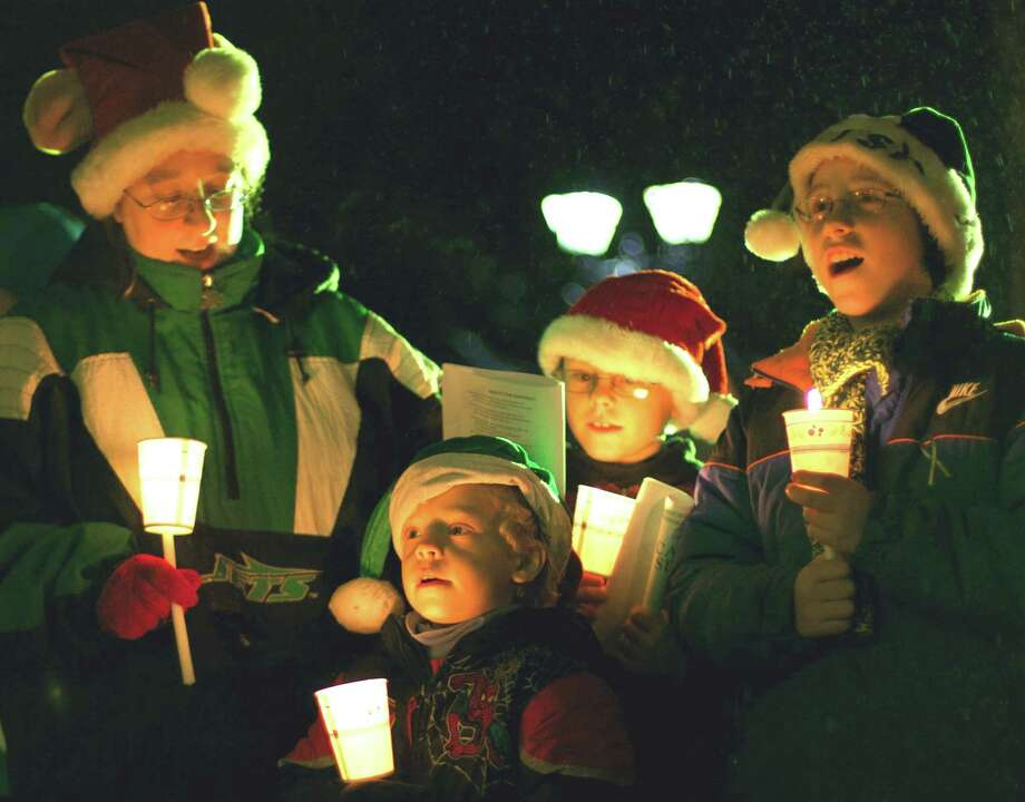 "'Deck The Halls'  Hundreds of Greater New Milford area residents joined the chorus Monday evening on the Village Green in New Milford for the Commission on the Arts' annual Carol Sing. A chilling drizzle fell on the carolers but that didn't dampen the holiday spirit of those on hand to sing and greet Santa Claus. Above, joining in the singing of ""Deck The Halls"" are Lisa Dugan and her sons, from left to right, Christopher, 5, Matthew, 9, and Brian, 11, of New Milford. For more photos, see the Dec. 28 edition of The Spectrum and visit www.newmilfordspectrum.com. Photo: Trish Haldin"