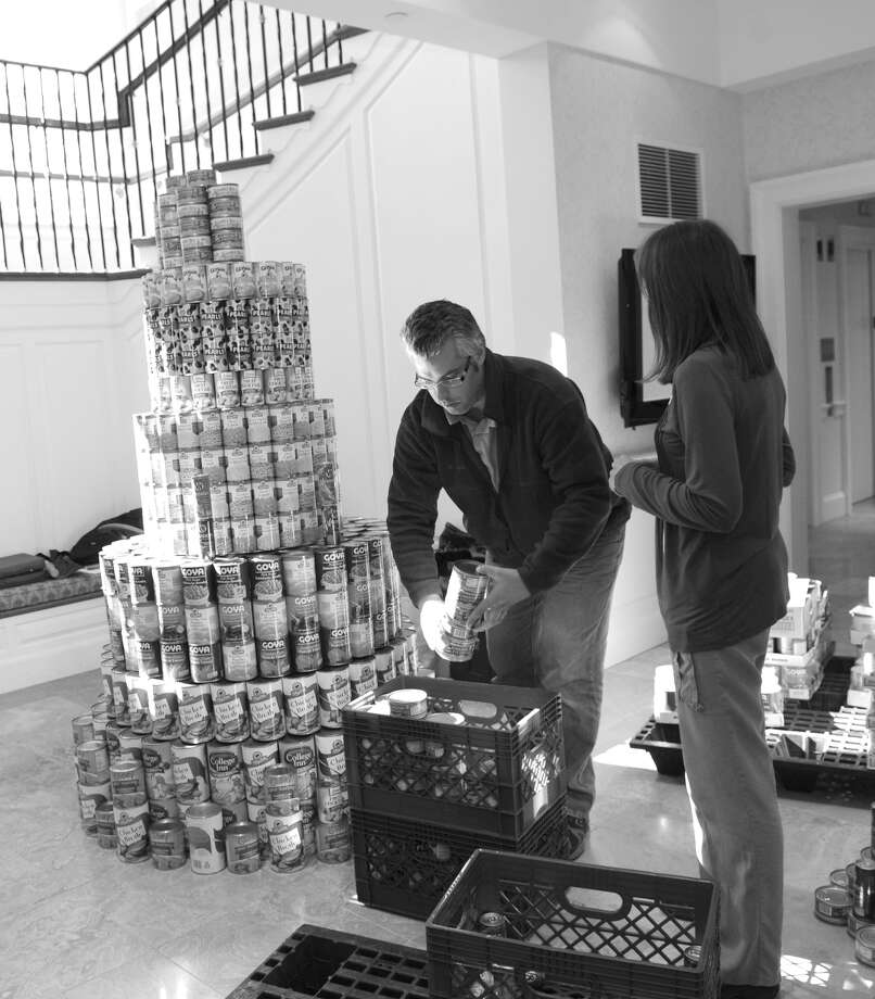 The first-ever Greenwich Canstruction competition was a great success according to event co-chairs Margie Black and Denise Dreskin. Here, Richard Basic and Laura Kaehler, from Greenwich-based Laura Kaehler Architects, make a sculpture out of cans for Girls Scouts Troop 50527 at Canstruction, which benefits Neighbor to Neighbor. Photo: Helen Neafsey / Greenwich Time