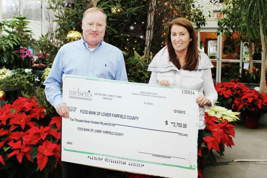 Jerry Nielsen and Sandy Nielsen-Baumann, both third-generation owners of Nielsen's Florist in Darien, display the check given to the Food Bank of Lower Fairfield County, which benefited from two events held at the establishment. Photo: Contributed
