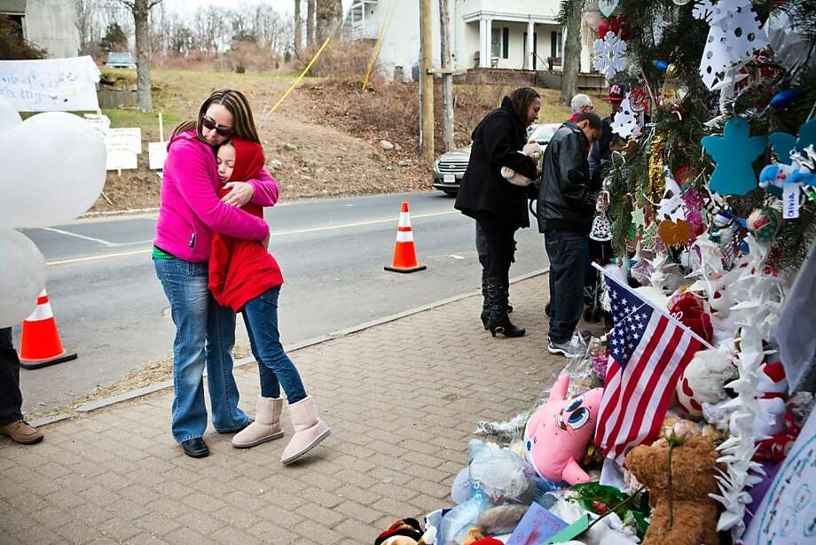 On Christmas Eve, Deborah Gibelli holds her daughter Alexandra, age 9, at a memorial for those killed in the shooting at Sandy Hook Elementary School in Newtown, Conn. Photo: Andrew Burton, Getty Images