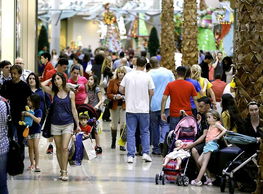 Holiday shoppers at the Mall at Millenia in Orlando - sales slowed in part from gridlock in Congress. Photo: John Raoux, Associated Press