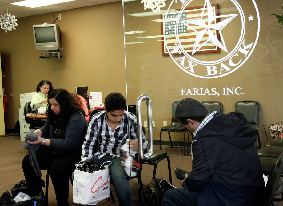 Julia Paramo, son Joaquin Capistran and husband Joaquin Capistran sort through purchases and receipts at a Texas Tax Back office, which helps international visitors get sales tax refunds. Photo: Helen L. Montoya, San Antonio Express-News / ©SAN ANTONIO EXPRESS-NEWS