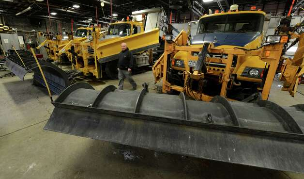 NYS DOT driver Lance Kramer walks between snow plows at the DOT offices in Latham, N.Y. Dec 26, 2012 after they vehicles are readied for the storm that is forecast for the Capital District tonight and tomorrow. (Skip Dickstein/Times Union) Photo: SKIP DICKSTEIN / 00020573A