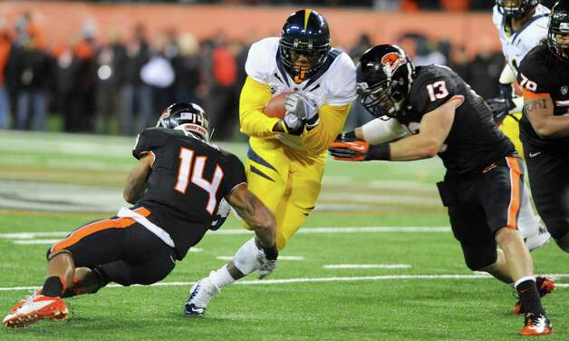 Oregon State's Jordan Poyer (14) and Reuben Robinson (13) tackle against California's C.J. Anderson (9) during the first half of an NCAA college football game in Corvallis, Ore., Saturday Nov.,17, 2012. (AP Photo/Greg Wahl-Stephens) Photo: Greg Wahl-Stephens, Associated Press / FR29287 AP