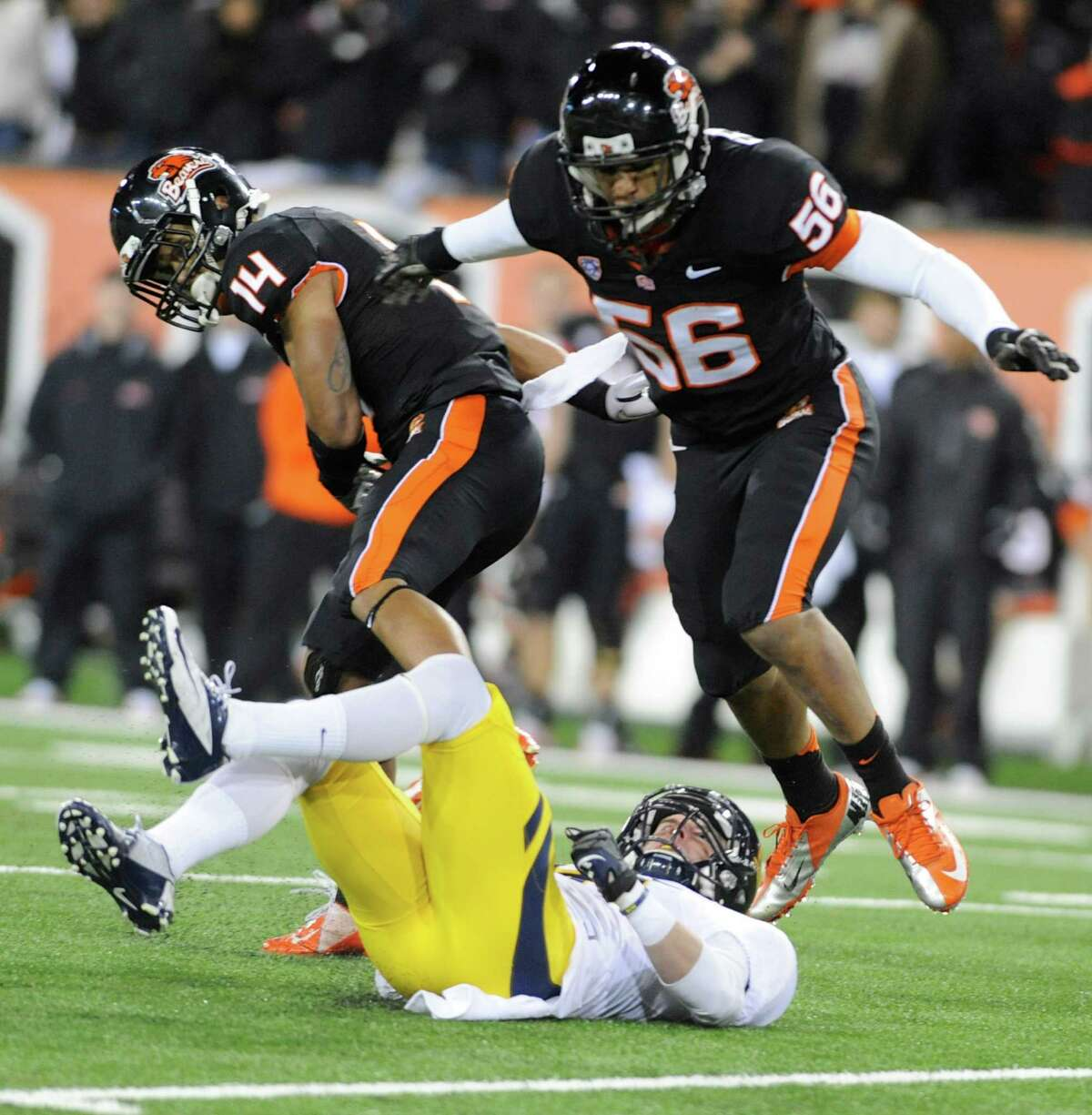 Oregon State's Jordan Poyer (14) and Rusty Fernando (56) break up a pass to California's Chris Harper (6) during the first half of an NCAA college football game in Corvallis, Ore., Saturday Nov.,17, 2012. (AP Photo/Greg Wahl-Stephens)