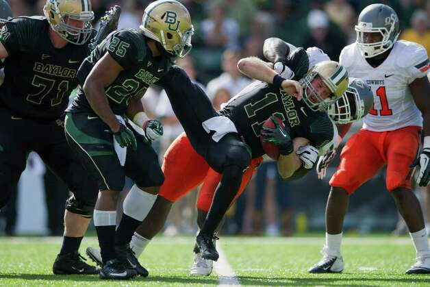 Nick Florence #11 of the Baylor University Bears is sacked by Calvin Barnett #99 of the Oklahoma State University Cowboys on December 1, 2012 at Floyd Casey Stadium in Waco, Texas. Photo: Cooper Neill, Getty Images / 2012 Getty Images