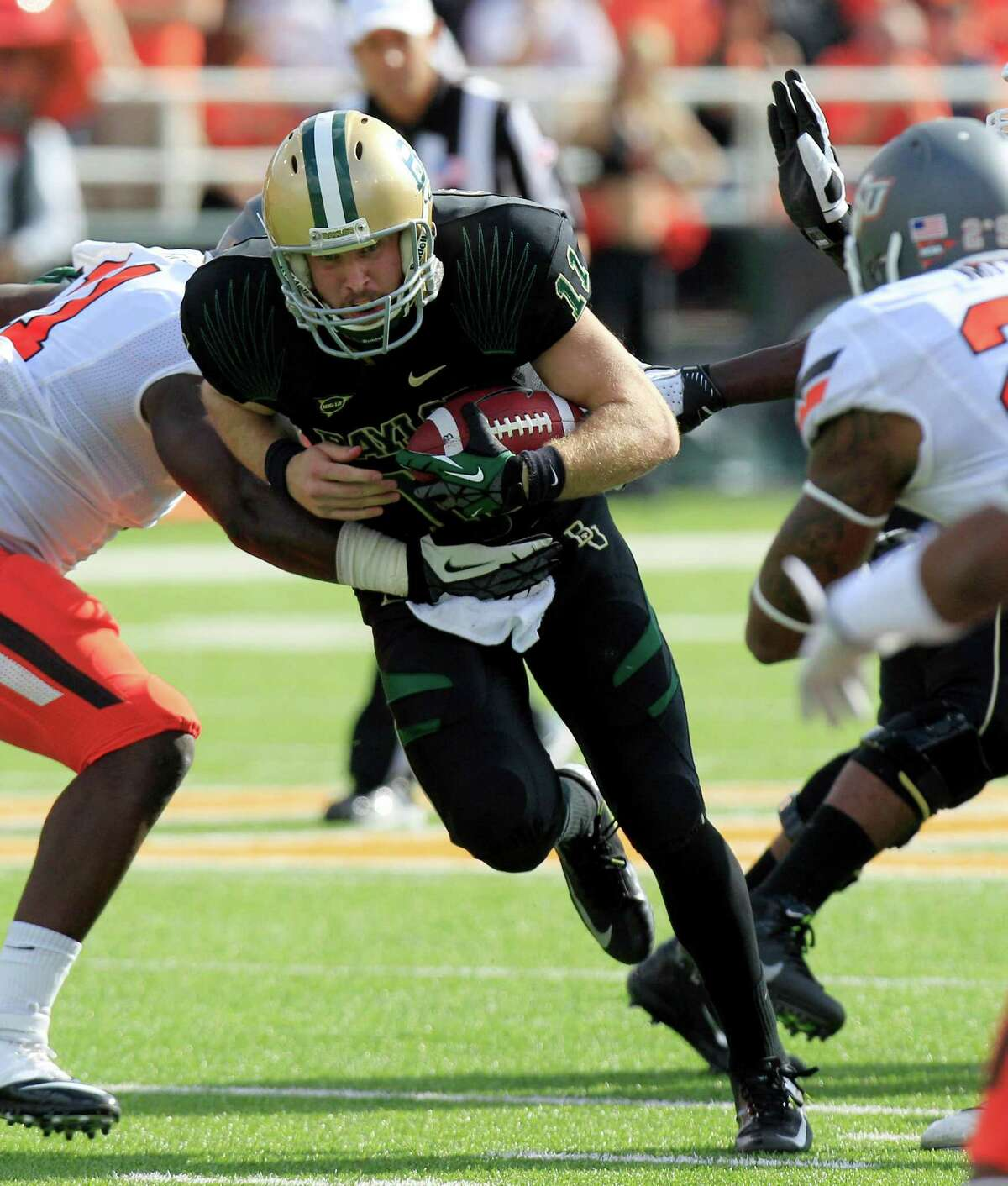 Baylor quarterback Nick Florence (11) runs on the keeper against Oklahoma State linebacker Shaun Lewis (11) during the second half of an NCAA college football game, Saturday, Dec. 1, 2012, in Waco, Texas. Baylor won 41-34. (AP Photo/LM Otero)