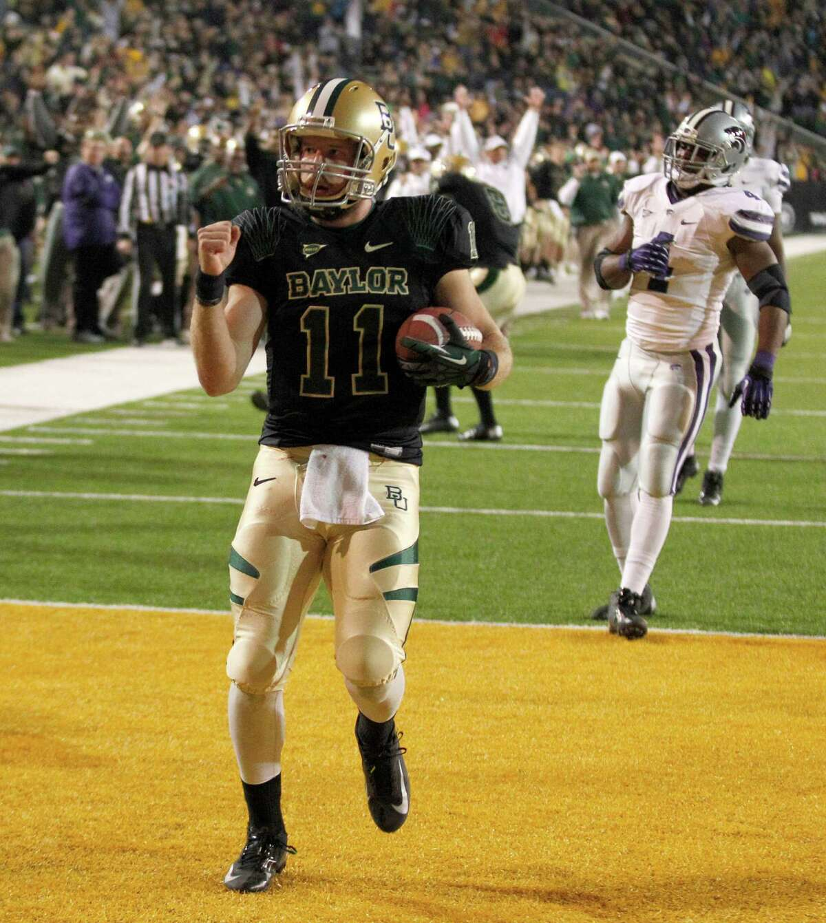 Baylor quarterback Nick Florence (11) scores a touchdown past Kansas State Wildcats linebacker Arthur Brown (4) during the first quarter of the NCAA college football game Saturday, Nov. 17, 2012, in Waco Texas. (AP Photo/LM Otero)