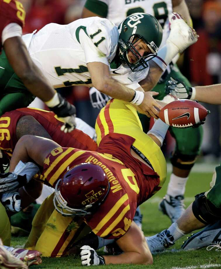 Baylor quarterback Nick Florence (11) fumbles the ball into the end zone over Iowa State defensive lineman Jake McDonough during the first half of an NCAA college football game, Saturday, Oct. 27, 2012, in Ames, Iowa.  Iowa State recovered the ball. (AP Photo/Charlie Neibergall) Photo: Charlie Neibergall, Associated Press / AP