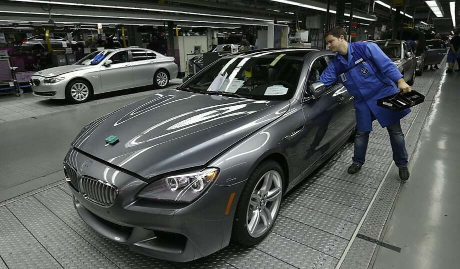 An employee works on a BMW on the production line of the car manufacturer's plant near Munich. Photo: Matthias Schrader, Associated Press