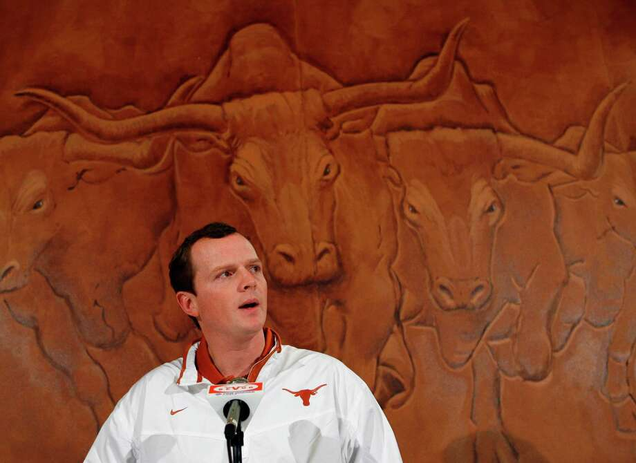Major Applewhite sits in front of a mural of stampeding Longhorns as he speaks during a news conference Thursday, Jan. 17, 2008, in Austin, Texas. It was announced that the former Texas quarterback, who became a folk hero with his cherubic looks and cool demeanor on the field, has returned to be the Longhorns running backs coach and assistant head coach. (AP Photo/Harry Cabluck) Photo: Harry Cabluck, Express-News / AP