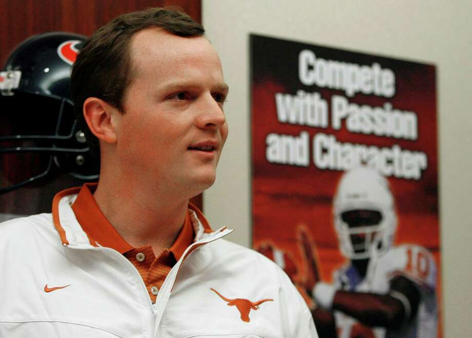 Major Applewhite stands near a poster featuring another former University of Texas quarterback as he waits to speak at a news conference Thursday, Jan. 17, 2008, in Austin, Texas. It was announced that Applewhite, who became a folk hero with his cherubic looks and cool demeanor on the field, has returned to be the Longhorns running backs coach and assistant head coach. (AP Photo/Harry Cabluck) Photo: Harry Cabluck, Express-News / AP