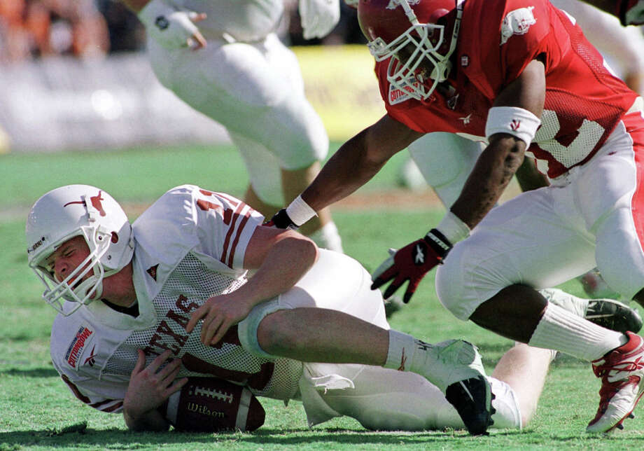Texas' quarterback Major Applewhite (11) winces as he is sacked by Arkansas' Jeremiah Harper (32) during the fourth quarter of the Cotton Bowl in Dallas, Saturday, Jan. 1, 2000. Applewhite was injured on the play in the 27-6 win by Arkansas. (AP Photo/Tim Sharp) Photo: TIM SHARP, Express-News / AP