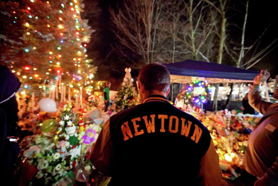 Greg Frattaroli, 19, of Newtown, Conn., visits a memorial for the Sandy Hook Elementary School shooting victims, Tuesday, Dec. 18, 2012, in Newtown, Conn. (AP Photo/David Goldman) Photo: David Goldman