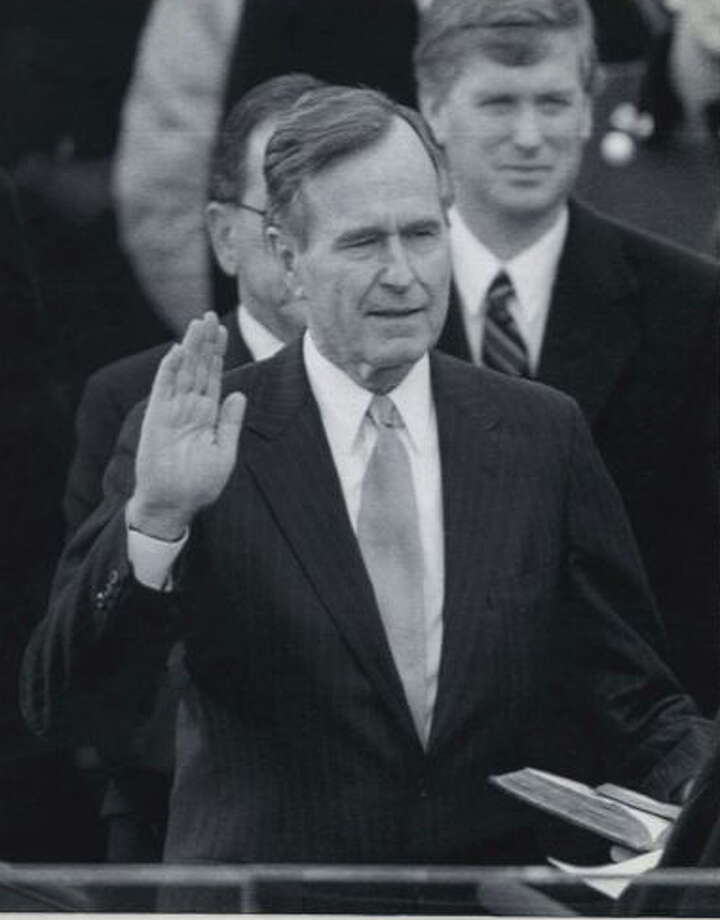 Bush takes the oath of office as  president of the United States in 1989. Vice  President Dan Quayle watches from behind.