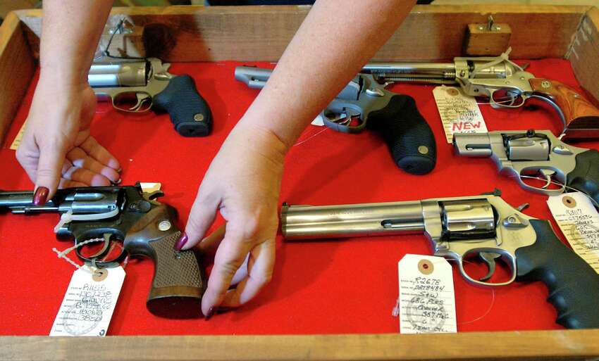 Linda Sehlmeyer, owner of The Gun Shop at MacGregor's in Lake Luzerne, places revolvers in a display case for the Arms Fair on Friday, Aug. 28, 2009, at the City Center in Saratoga Spring, N.Y. (Cindy Schultz / Times Union)