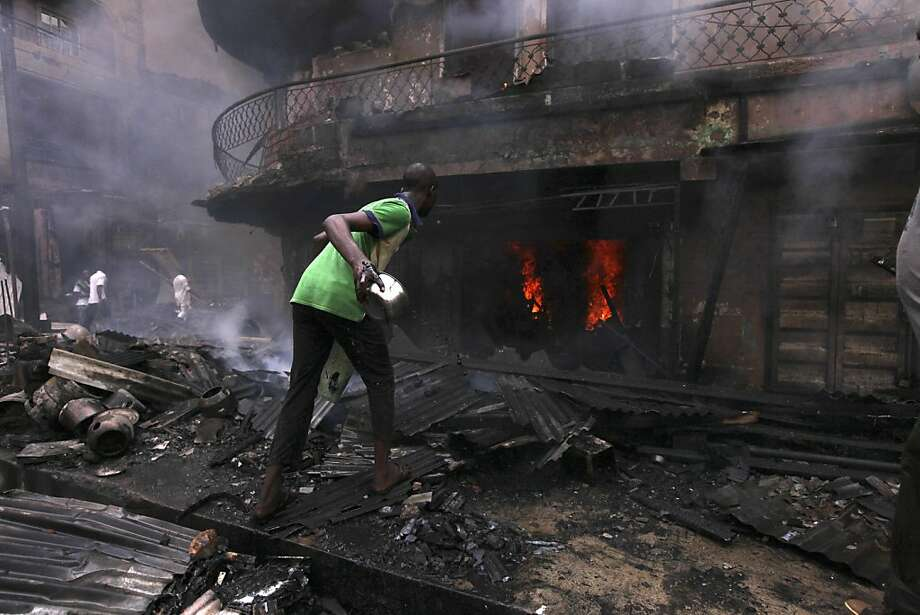 A man throws a pot of water on a fire burning a home in a Lagos, Nigeria, neighborhood, where firefighters quickly ran out of water trying to douse the blaze ignited by the fireworks blast. Photo: Sunday Alamba, Associated Press