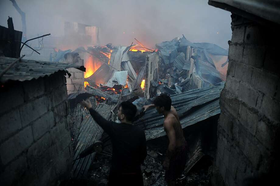 Residents look at destroyed houses as they smolder after a pre-dawn fire engulfed a slum area in Manila on December 25, 2012. At least seven people were killed and thousands left homeless as two fires struck the Philippine capital on Christmas Day, sparking riots as a slum went up in flames, Manila's fire marshal said. Photo: Noel Celis, AFP/Getty Images