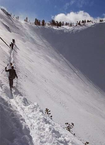 In this file photo,  skiers cut a path across the top of Red Cone, a snow bowl along the crest of the Sierra Nevada mountain range, west of Mammoth Lakes, Calif., Dec. 6, 1998. The backcountry skiers wore avalanche beacons and carried shovels in the event of an avalanche. Photo: Martha Bellisle, Associated Press