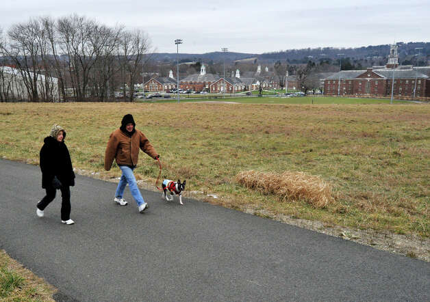 Deb and Louis Altieri walk their dog, Benny, along the trail system behind Fairfield Hills Campus in Newtown on Wednesday, Dec. 26, 2012. Photo: Jason Rearick / The News-Times