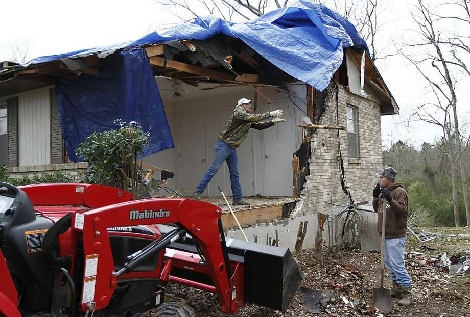 Michael Donaldson (left) and Michael Lane clear away debris from a damaged home in Centreville, Miss., after intense storms that wreaked destruction and shut down traffic. Photo: Philip Hall, Associated Press