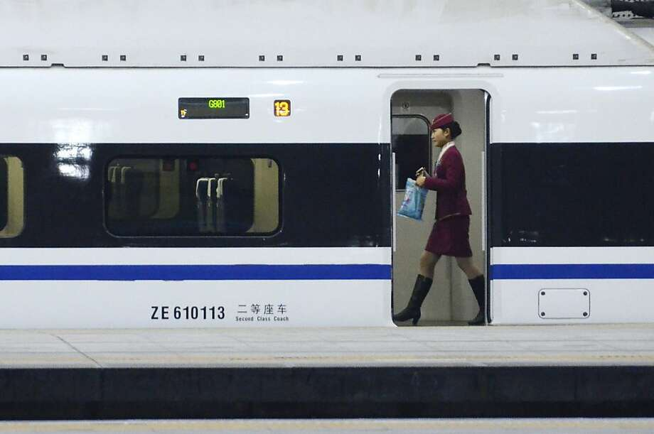 A stewardess walks inside a high-speed train running from the Beijing to Guangzhou, south China's Guangdong province, at the Beijing west railway station in Beijing on December 26, 2012. China on December 26 started service on the world's longest high-speed rail route, the latest milestone in the country's rapid and sometimes troubled super fast rail network. Photo: Wang Zhao, AFP/Getty Images