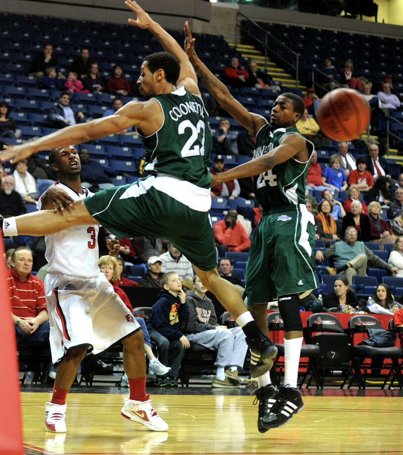 Highlights from men's basketball action between Fairfield University and Manhattan College at the Webster Bank Arena in Bridgeport, Conn. on Thursday February 9, 2012. Fairfield University's #3 Derek Needham, left, passes the ball through two blocking Manhattan College players. Photo: Christian Abraham / Connecticut Post