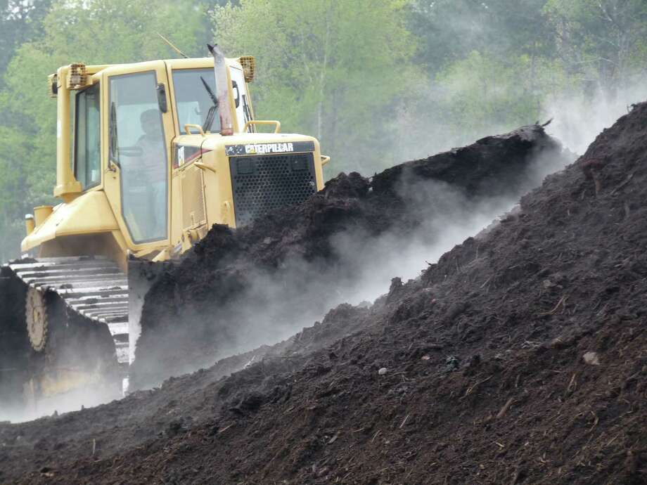 A bulldozer turns a pile of compost - which must contain the right mix of soil, organic material, food waste, bacteria and fungi.