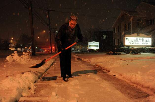 Bill Mortimer shovels the sidewalk in front of the McDonald Funeral Home in Stratford, Conn. Wednesday, Dec. 26, 2012. Photo: Autumn Driscoll / Connecticut Post