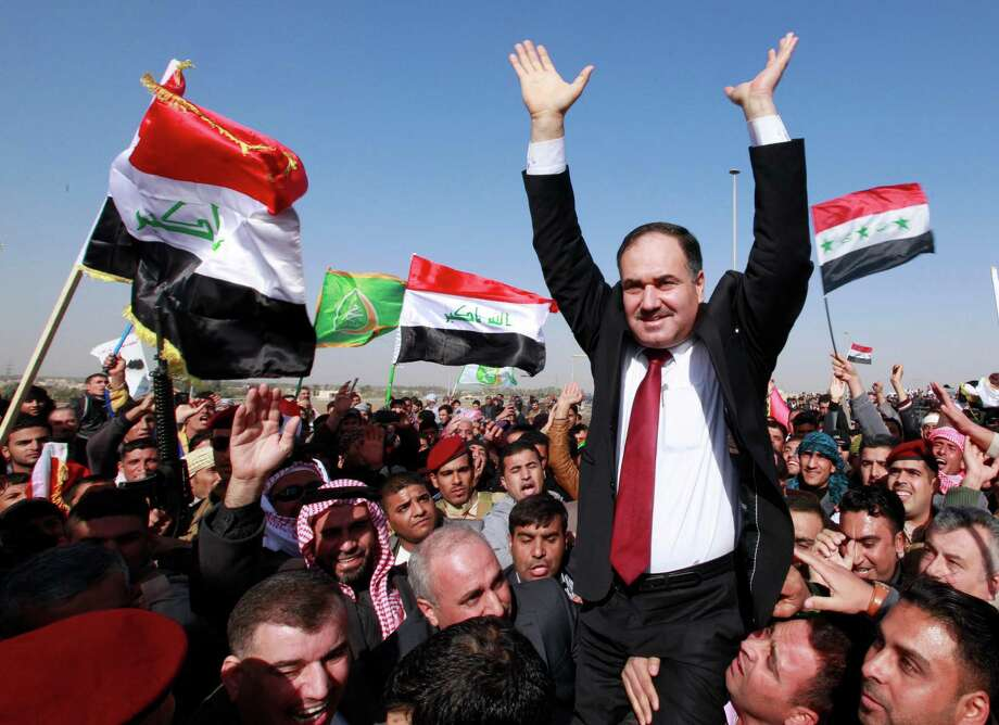 Iraq's Finance Minister Rafia al-Issawi is carried by his supporters during a demonstration in Ramadi, 70 miles (115 kilometers) west of Baghdad, Iraq, Wednesday, Dec. 26, 2012. Thousands of Iraqi demonstrators massed in a Sunni-dominated province west of Baghdad Wednesday, determined to keep up the pressure on a Shiite-led government that many accuse of trying to marginalize them. (AP Photo/ Hadi Mizban) Photo: Hadi Mizban